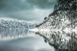 Image of a lake with mountains and snow.