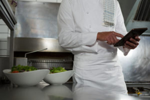 Mid-section of male chef using mobile phone in the kitchen for cutting hospitality food waste.