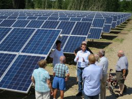 A group of people inspecting solar panels.
