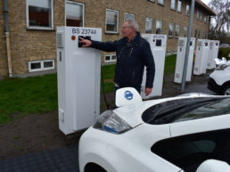 Man from Bornholm Municipality charging an electric vehicle. ACES.