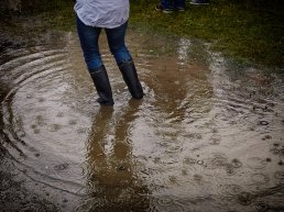 Woman surrounded by a puddle due to climate change.