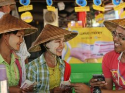 Men and women in Myanmar. using the Wave Money cellphone application for financial transactions.