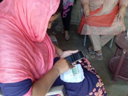 Woman using the Telenor app for birth registration.
